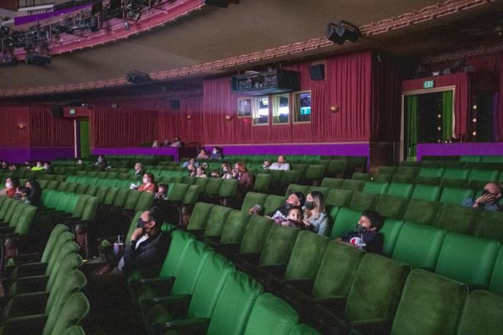 Movie-goers spread out with COVID-19 safety precautions in effect at The El Capitan Theatre in Hollywood.