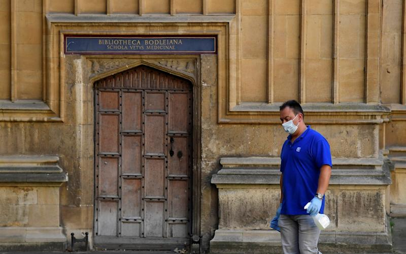 A man carrying cleaning materials walks through the quadrangle of the Old Bodleian Library buildings, Oxford University