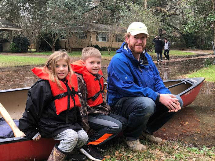 Nate Green and his children, Owen, 8, and Anna Kate, 6, use a canoe to navigate the streets of Jackson, Miss., on Feb. 16.