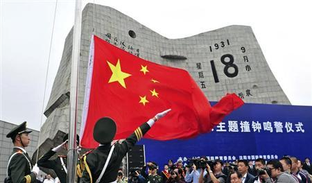 Paramilitary policemen hoist a Chinese national flag during a memorial ceremony on the 82nd anniversary of Japan's invasion of China at the September 18 Museum in Shenyang