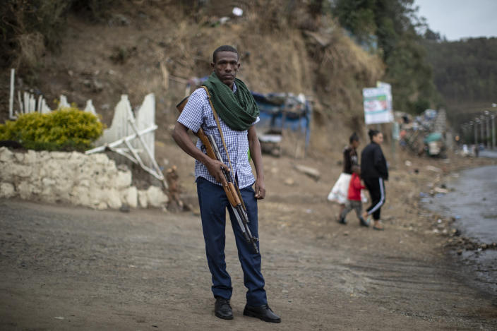 Amhara militia member Nega Wagaw poses for a photograph on a street in Gondar, in the Amhara region of Ethiopia Sunday, May 2, 2021. Ethiopia faces a growing crisis of ethnic nationalism that some fear could tear Africa's second most populous country apart, six months after the government launched a military operation in the Tigray region to capture its fugitive leaders. (AP Photo/Ben Curtis)