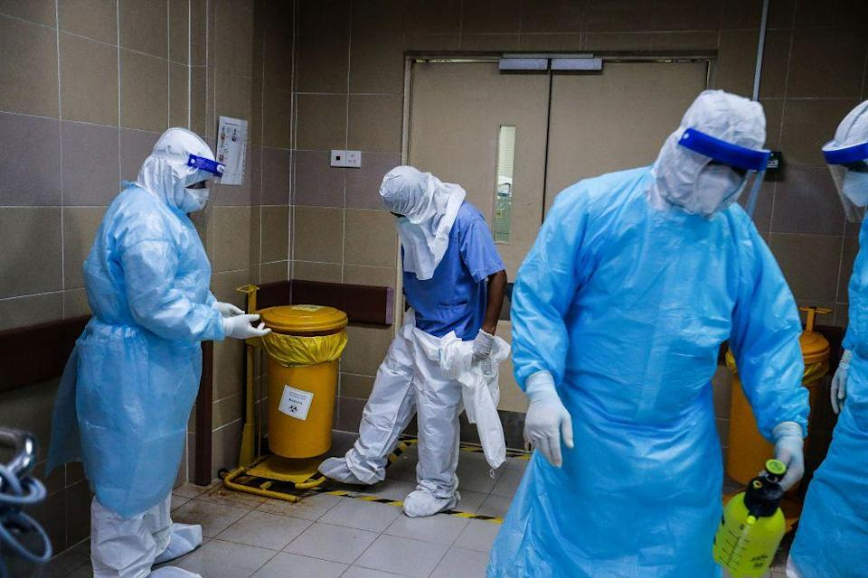 Forensics personnel don full personal protective gear as they prepare the body of a recently deceased Covid-19 patient for burial at the Penang General Hospital, August 24, 2021. — Picture by Sayuti Zainudin