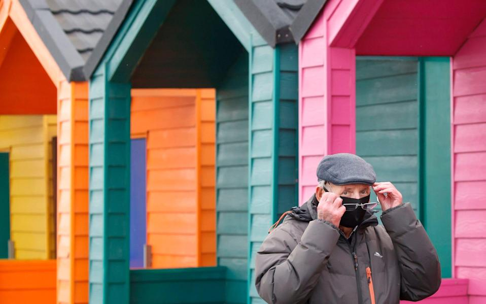 A man wears a face covering as he walks past beach huts in Saltburn-by-the-Sea - Danny Lawson / PA