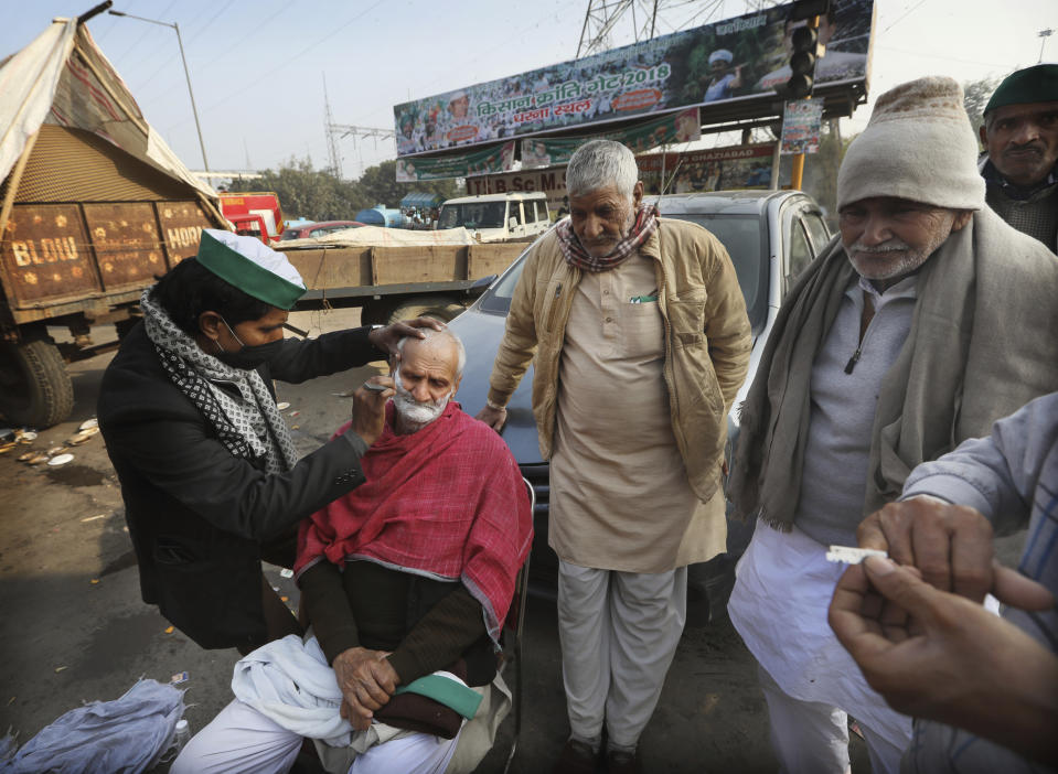 An Indian farmer gets a shave as they block a highway in protest against new farm laws at the Delhi-Uttar Pradesh state border, on the outskirts of New Delhi, India, Wednesday, Dec. 30, 2020. Protesting farmers fear the government will stop buying grain at minimum guaranteed prices and corporations will then push down prices. The government says the three laws approved by Parliament in September will enable farmers to market their produce and boost production through private investment. (AP Photo/Manish Swarup)