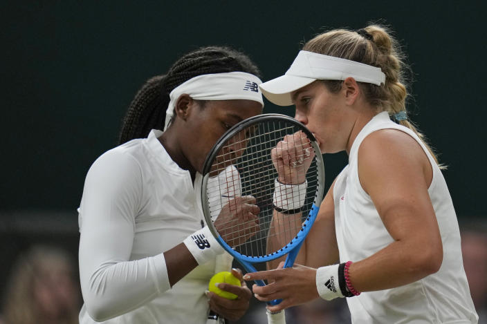 Coco Gauff of the U.S., left, and compatriot Caty McNally speak during the women's doubles third round match against Russia's Veronika Kudermetova and Elena Vesnina on day eight of the Wimbledon Tennis Championships in London, Tuesday, July 6, 2021. (AP Photo/Kirsty Wigglesworth)