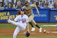 Los Angeles Dodgers starting pitcher Dustin May, left, avoids getting hit by a comeback shot hit by San Diego Padres' Eric Hosmer during the second inning of a baseball game Monday, Aug. 10, 2020, in Los Angeles. (AP Photo/Mark J. Terrill)