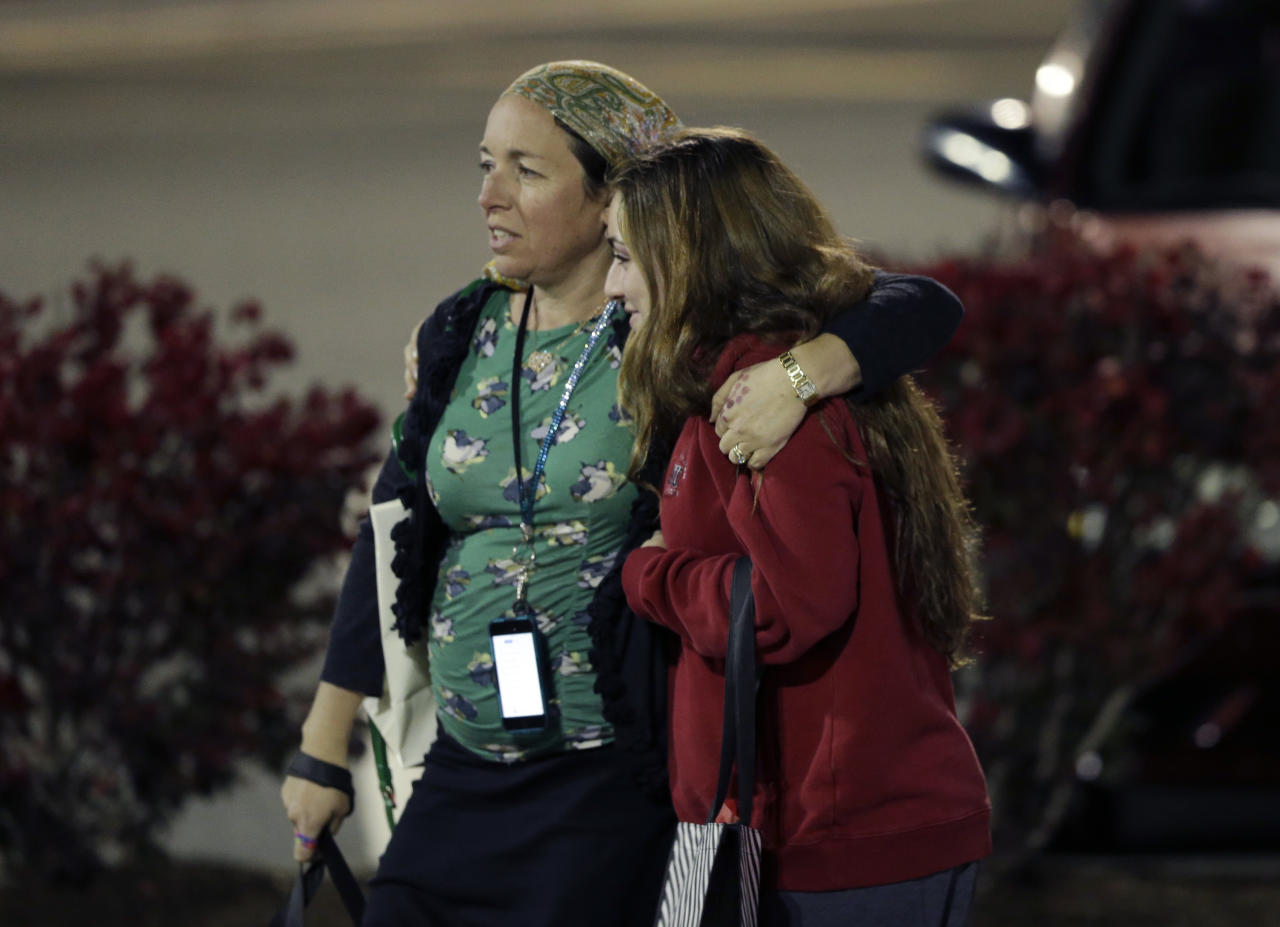 Two women walk in the parking lot of the Garden State Plaza Mall with officials standing guard following reports of a shooter, Monday, Nov. 4, 2013, in Paramus, N.J. Hundreds of law enforcement officers converged on the mall Monday night after witnesses said multiple shots were fired there. (AP Photo/Julio Cortez)