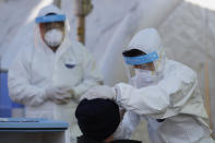 A medical worker wearing protective gear takes a sample from a man at a coronavirus/COVID-19 testing site in Seoul, South Korea, Sunday, Dec. 20, 2020. (AP Photo/Lee Jin-man)
