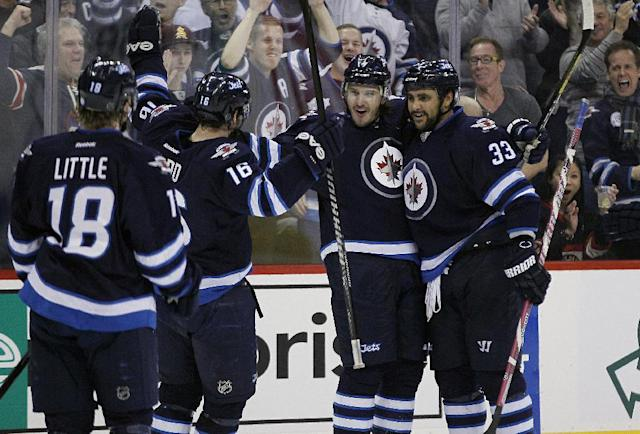 Winnipeg Jets' Bryan Little (18), Andrew Ladd (16), Keaton Ellerby, second from right, and Dustin Byfuglien (33) celebrate Ellerby's goal against the Chicago Blackhawks during the second period of an NHL hockey game in Winnipeg, Manitoba on Thursday, Nov. 21, 2013. (AP Photo/The Canadian Press, John Woods)