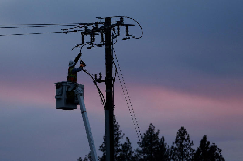 FILE - In this Nov. 26, 2018, file photo, a Pacific Gas & Electric lineman works to repair a power line in fire-ravaged Paradise, Calif. Two years to the day after some of the deadliest wildfires tore through Northern California wine country, two of the state's largest utilities were poised Tuesday, Oct. 8, 2019, to shut off power to more than 700,000 customers in 37 counties, in what would be the largest preventive shut-off to date as utilities try to head off wildfires caused by faulty power lines. (AP Photo/Rich Pedroncelli, File)