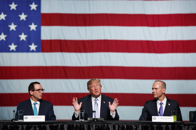 Treasury Secretary Steve Mnuchin, left, and Boeing CEO Dennis Muilenburg, right, listen as President Donald Trump speaks during a roundtable discussion on tax policy at the Boeing Company, Wednesday, March 14, 2018, in St. Louis. (AP Photo/Evan Vucci)