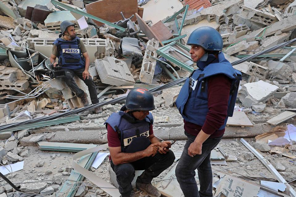 Journalists stand among the ruins of their officesAFP via Getty Images