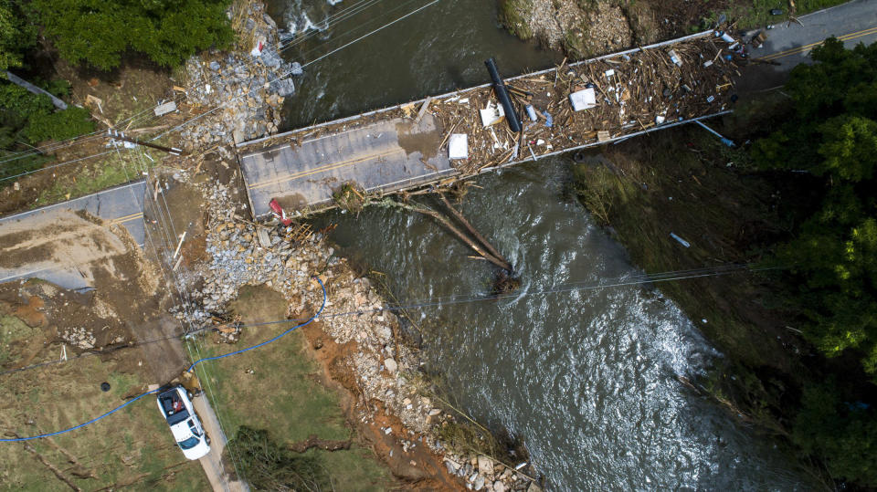 In this image taken with a drone, a flood-damaged bridge spans the Pigeon River, Thursday, Aug. 19, 2021, in Bethel, N.C., after remnants from Tropical Storm Fred caused flooding in parts of Western North Carolina Tuesday. (Travis Long/The News & Observer via AP)