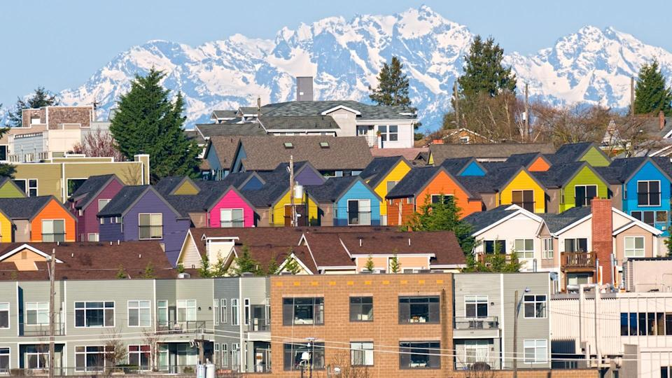 Row of colorful townhouses and Olympic Mountain range from Seattle WA.