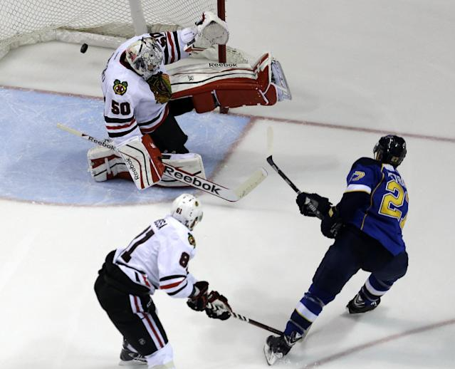 St. Louis Blues' Alex Pietrangelo, right, scores past Chicago Blackhawks goalie Corey Crawford (50) as Blackhawks' Marian Hossa, of Slovakia, watches during the third period in Game 5 of a first-round NHL hockey playoff series Friday, April 25, 2014, in St. Louis. (AP Photo/Jeff Roberson)