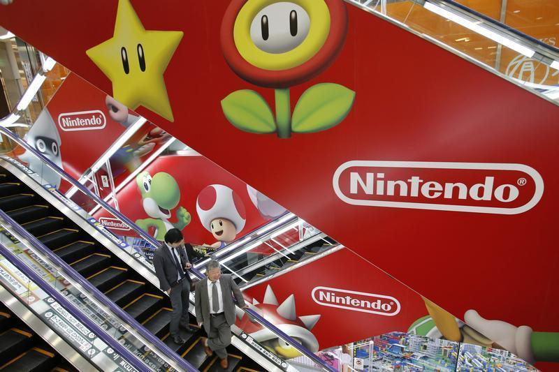 Men ride an escalator past Nintendo Co advertisements at an electronics retail store in Tokyo