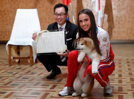 Russian figure skating gold medallist Alina Zagitova and Endo Takashi, head of the Association for the preservation of the purity of the Akito breed, pose with an Akita Inu puppy presented to her in Moscow, Russia May 26, 2018. REUTERS/Maxim Shemetov