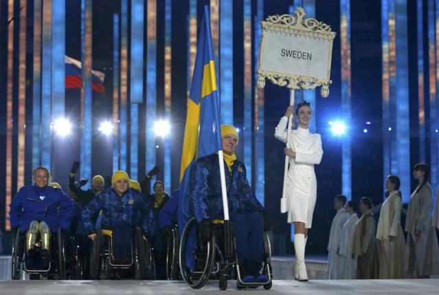 Sweden's flag-bearer Jalle Jungnell (C), leads his country's contingent during the opening ceremony of the 2014 Paralympic Winter Games in Sochi, March 7, 2014. REUTERS/Alexander Demianchuk (RUSSIA - Tags: OLYMPICS SPORT)