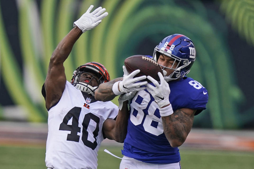 New York Giants tight end Evan Engram (88) catches a pass against Cincinnati Bengals safety Brandon Wilson (40) during the second half of NFL football game, Sunday, Nov. 29, 2020, in Cincinnati. (AP Photo/Bryan Woolston)