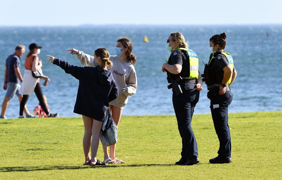 Police speak to people enjoying the unusually warm spring weather at St Kilda Beach as the city remains in lockdown. Source: Getty