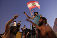 Anti-government protesters wave a Lebanese flag and shout slogans against the Lebanese government during a protest in Beirut, Lebanon, Monday, Oct. 21, 2019. Lebanon's Cabinet approved Monday sweeping reforms that it hopes will appease thousands of people who have been protesting for five days, calling on Prime Minister Saad Hariri's government to resign. (AP Photo/Hassan Ammar)