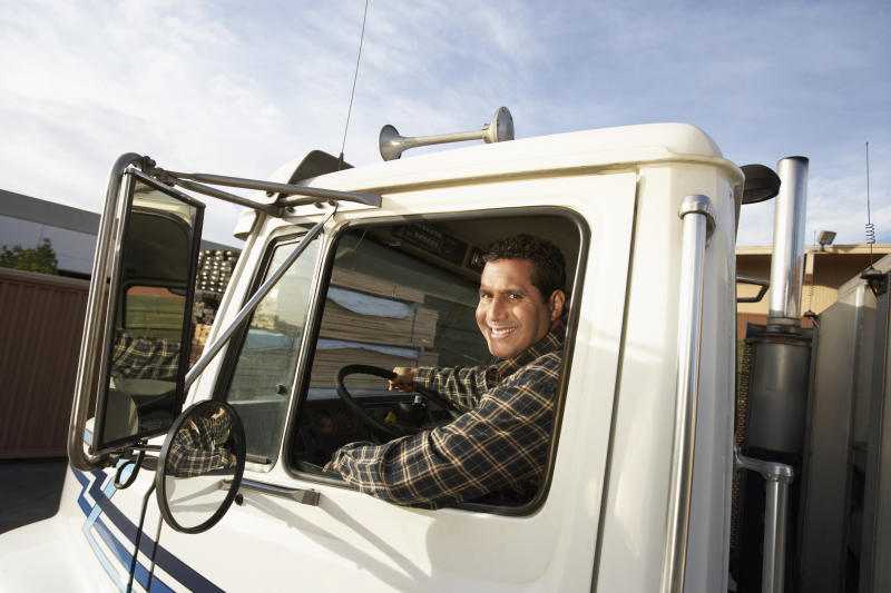 A truck driver smiling out the window of his cab