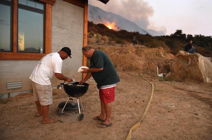 """Jeremy Anglin, left, and Matt Taylor heat up tacos on a grill as the El Dorado fire approaches in Yucaipa Saturday. The two men are friends of the homeowner and came to help fight the blaze if it got closer. <span class=""""copyright"""">(Wally Skalij / Los Angeles Times)</span>"""