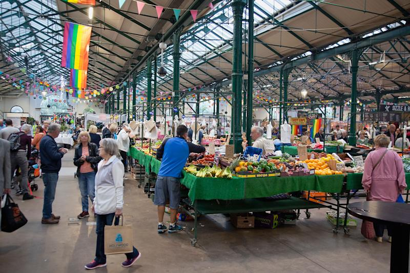 Ireland, North, Belfast, St George's Market interior, Fruit and veg stalls with rainbow flags above. (Photo by: Eye Ubiquitous/UIG via Getty Images)