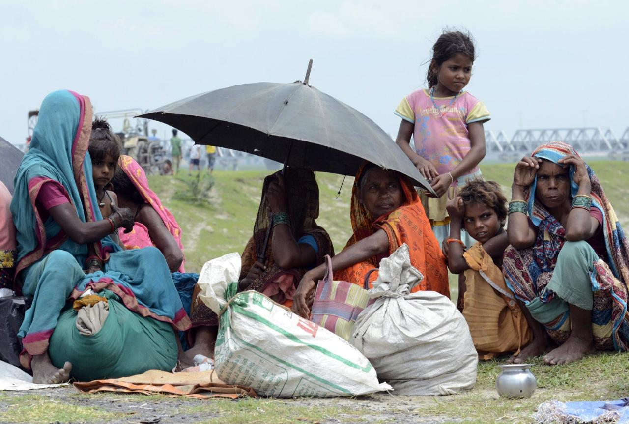 Villagers with their belongings sit in a relief camp after their evacuation at Supaul district in the eastern Indian state of Bihar August 3, 2014. More than 400,000 people in eastern India face the risk of flooding after a landslide that killed at least nine people in neighboring Nepal, an Indian government official said on Sunday, as thousands were being evacuated. The landslide triggered by heavy rains has left scores of people missing and has created a mud dam blocking the Sunkoshi river, which runs into India's Bihar state as the Kosi river. REUTERS/Krishna Murari Kishan (INDIA - Tags: ANIMALS SOCIETY DISASTER)
