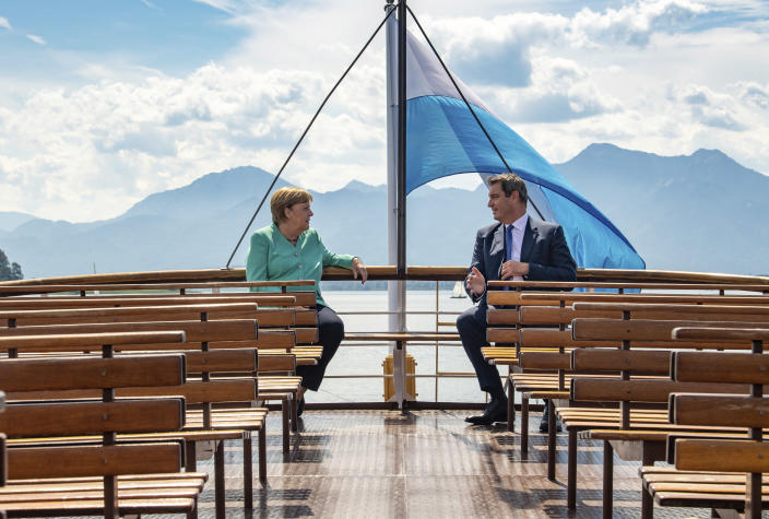 FILE - In this Tuesday, July 14, 2020 file photo, German Chancellor Angela, left, and Markus Soeder, right, Governour of the German state of Bavaria, talk during a boat tour in Priem Am Chiemsee, Germany. Markus Soeder is many things: state governor of Bavaria, Star Trek fan, a conservative for whom combating climate change is an article of faith. The question Germans are asking now is: can the 54-year-old win enough backing across the political spectrum to succeed Angela Merkel as chancellor in September. (Peter Kneffel/DPA via AP, Pool, file)