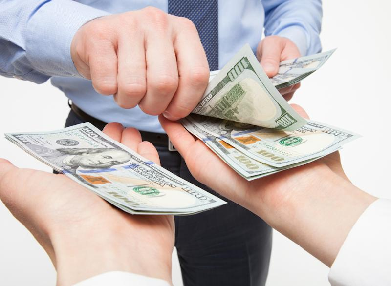 A businessmen in a tie placing crisp hundred dollar bills into two outstretched hands.