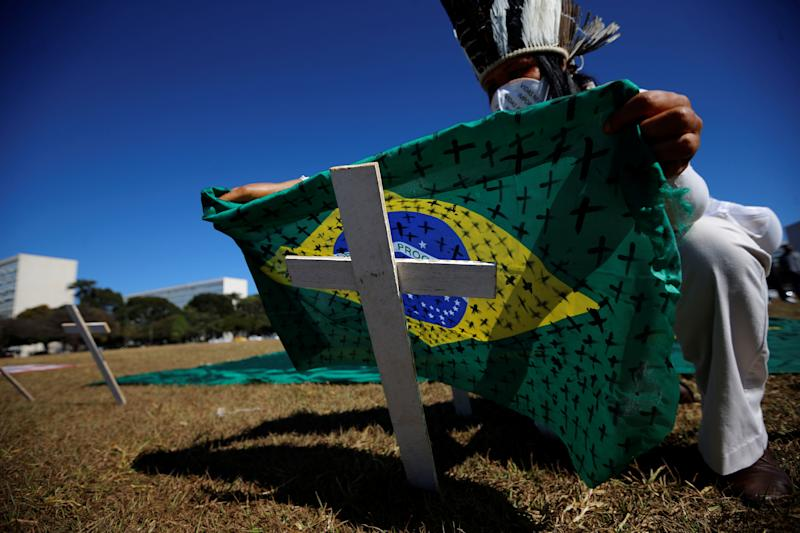 An activist puts a Brazilian flag painted with crosses on a cross symbolising those who died of the coronavirus disease (COVID-19) in front of the National Congress during a protest against the President of Brazil, Jair Bolsonaro, in Brasilia, July 14, 2020. REUTERS/Adriano Machado