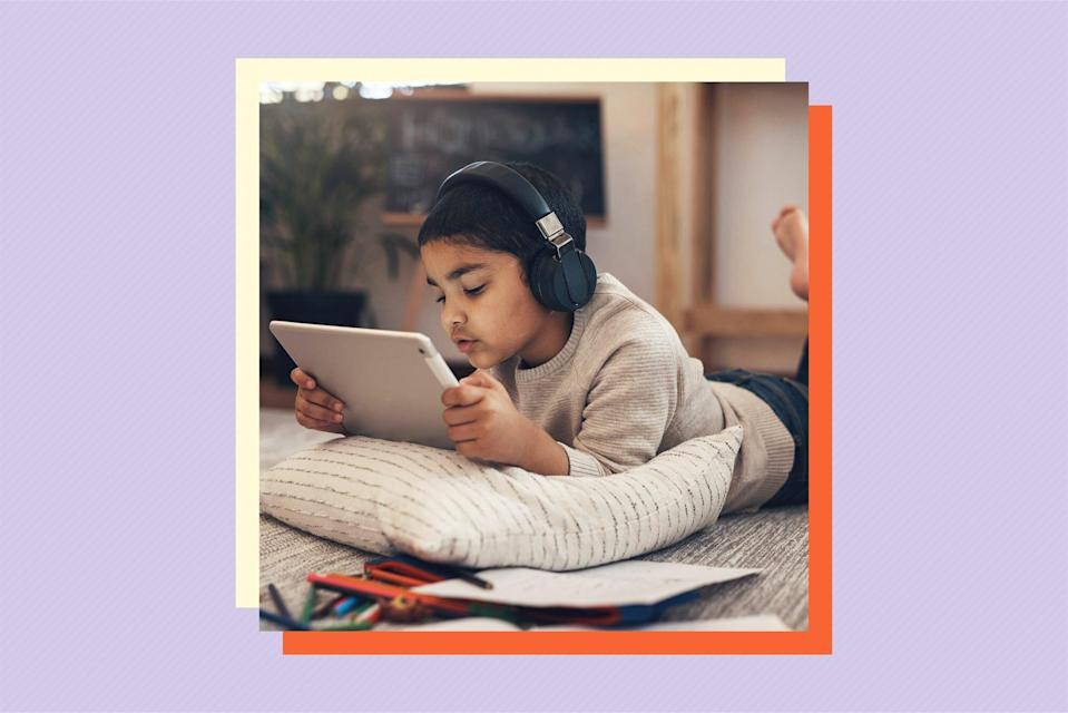 child lying on floor while using tablet and wearing headphones