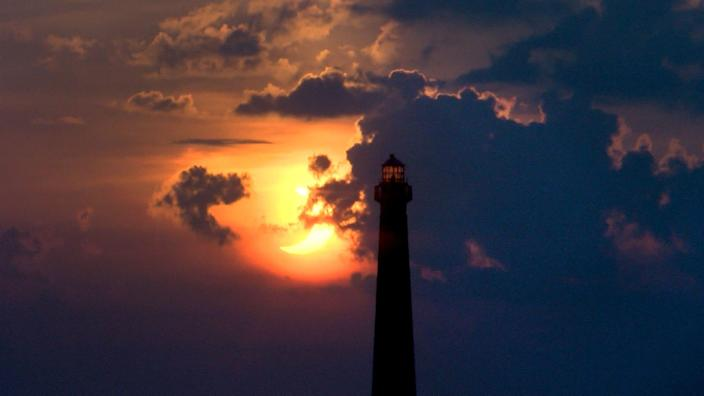 The solar eclipse rises behind the Barnegat Lighthouse as seen from High Bar Harbor, N.J.
