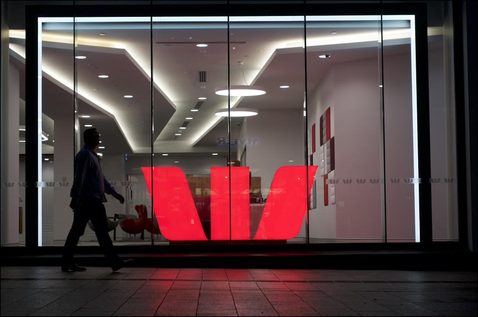 Brisbane, Queensland, Australia - 27th November 2019 : View of an illuminated Westpac logo behind a glass wall in the Queenstreet mall in Brisbane, while a man is passing by