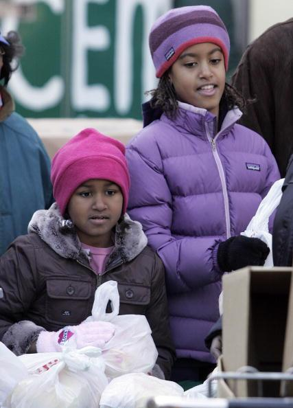 Sasha Obama (L) and Malia Obama, daughters of President-elect Barack Obama, pass out food at St. Columbanus Parrish and School November 26, 2008, in Chicago, Illinois. Obama earlier intruduced Paul Volckeras the chair of his Economic Recovery Advisory Board. (Photo by Frank Polich-Pool/Getty Images)