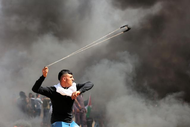 <p>A Palestinian protester uses a sling shot during clashes with Israeli toops near the border with Israel in the east of Jabaliya refugee camp in the northern Gaza Strip, April 6, 2018. (Photo: Momen Faiz/NurPhoto via Getty Images) </p>