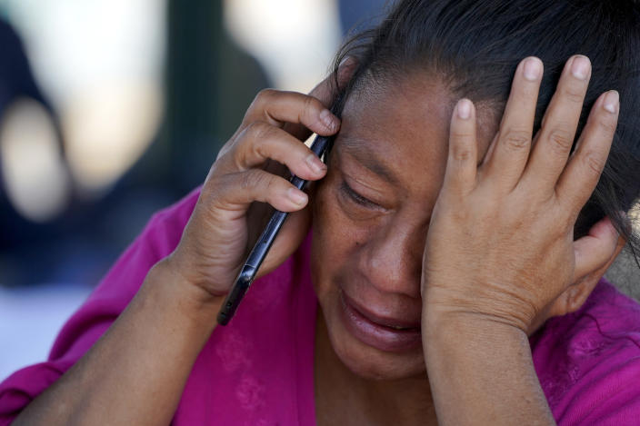 A migrant woman cries as she talks on a cellphone at a park after she and a large group of migrants who were expelled from the U.S. were pushed by Mexican authorities off an area they had been staying after their expulsion, Saturday, March 20, 2021, in Reynosa, Mexico. (AP Photo/Julio Cortez)
