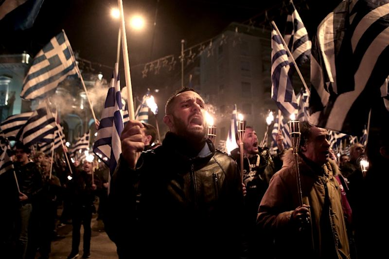 Members of the Greek ultra nationalist party Golden Dawn shout slogans, holding Greek national flags and torches on January 31, 2015 in Athens (AFP Photo/Angelos Tzortzinis)