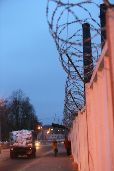 This Monday, Dec. 3, 2012 photo shows the Borisovdrev wood-processing plant, whose surrounding high walls are topped with barbed wire, in the industrial city of Borisov, about 50 kilometers (30 miles) east of the Belarusian capital, Minsk. Belarus' authoritarian president, Alexander Lukashenko, has decided to stem an exodus of qualified workers to Russia, starting by banning those who work in wood-processing industries from quitting. Critics have compared the measure to serfdom and warned that it would only deepen the former Soviet republic's economic troubles and fuel protests against Lukashenko. (AP Photo/Sergei Grits)