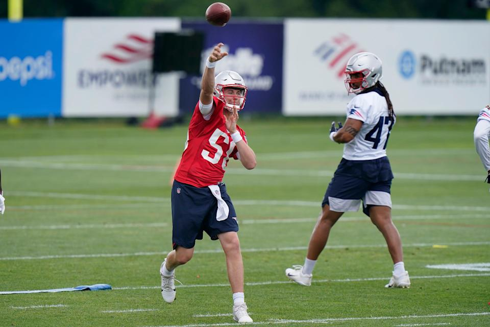 New England Patriots quarterback Mac Jones (50) passes the ball as fullback Jakob Johnson (47) looks on during an NFL football minicamp practice, Tuesday, June 15, 2021, in Foxborough, Mass.