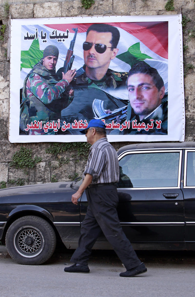 "In this Tuesday, April. 30, 2013 photo, a Lebanese man passes in front of a large poster of Syrian President Bashar Assad, center, and two Alawite fighters killed in Syria with Arabic writing that reads, ""at your service, oh Assad,"" and, ""bullets will not terrify us and we are not scared of traitors,"" in the predominantly Alawite neighborhood of Jabal Mohsen in the northern port city of Tripoli, Lebanon.  Lebanese members of the Syrian leader's Alawite sect fear their tiny community will be a casualty of the civil war raging in the neighboring country. Already, Sunni extremists have stoned a school bus, vandalized stores and beaten or stabbed a number of men in a wave of attacks against Lebanese Alawites, raising fears of more violence should Assad be removed from power. (AP Photo/Bilal Hussein)"
