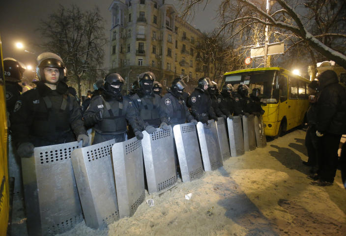 Ukrainian riot police guard the Ukrainian Government buildings in Kiev, Ukraine, early Tuesday, Dec. 10, 2013. Heavily armed riot troops broke into the offices of a top Ukrainian opposition party in Kiev and seized its servers Monday, the party said, as anti-government protests crippled the capital for yet another day. Elsewhere police dismantled or blocked off several small protest tent camps set up near key national government buildings in the city. (AP Photo/Sergei Grits)