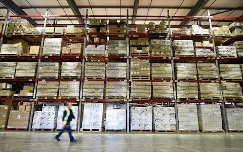 <span>A warehouse worker passes NHS medicine stockpiles in Wales</span> <span>Credit: Ben Birchall/ PA </span>