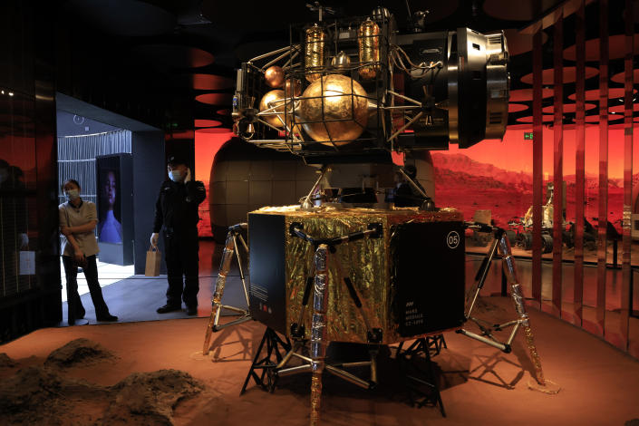 A security guard and worker stand near a depiction of a Chinese lander in a Mars-like environment in Beijing on Friday, May 14, 2021. China says its Mars probe and accompanying rover are to land on the red planet sometime between early Saturday morning and Wednesday Beijing time. (AP Photo/Ng Han Guan)