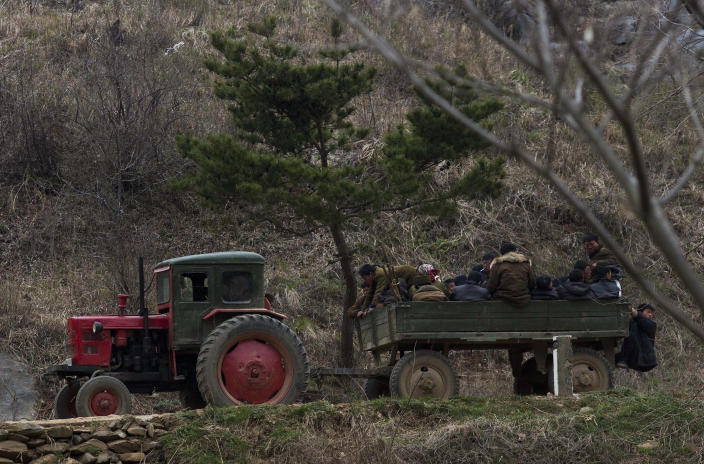 In this April 23, 2013 photo, North Korean farmers ride in the back of a tractor drawn wagon near Kaesong, North Korea. Farmers in North Korea have confirmed that they have begun carrying out new economic policies designed to boost productivity by giving managers and workers financial incentives. Some foreign analysts say the moves are reminiscent of early reform in China in the late 1970s. (AP Photo/David Guttenfelder)