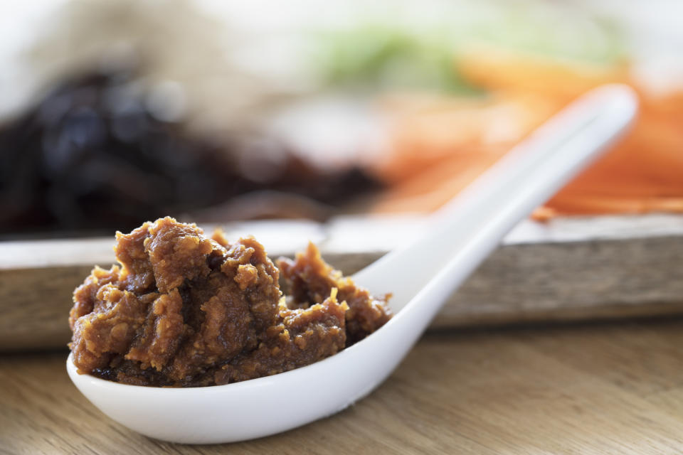 Close up of red miso paste in a Chinese soup spoon.