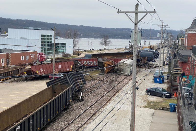 This photo provided by Ryan Burchett of the Mississippi River Drilling Company, shows a train derailment Friday, Jan. 3, 2020, that sent at least a dozen rail cars and tankers off their tracks in downtown LeClaire, Iowa. The derailment forced police to shut down the highway and send a hazardous materials team to the site. (Ryan Burchett/Mississippi River Drilling Co. via AP)
