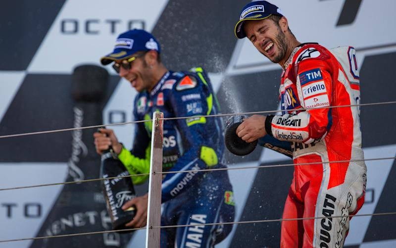Andrea Dovizioso (right) sprays the champagne after winning last time out at Silverstone to reclaim the lead in the title race - but all the news ahead of this weekend's race at Misano concerns Valentino Rossi (left) who has broken a leg in a training accident - Action Plus