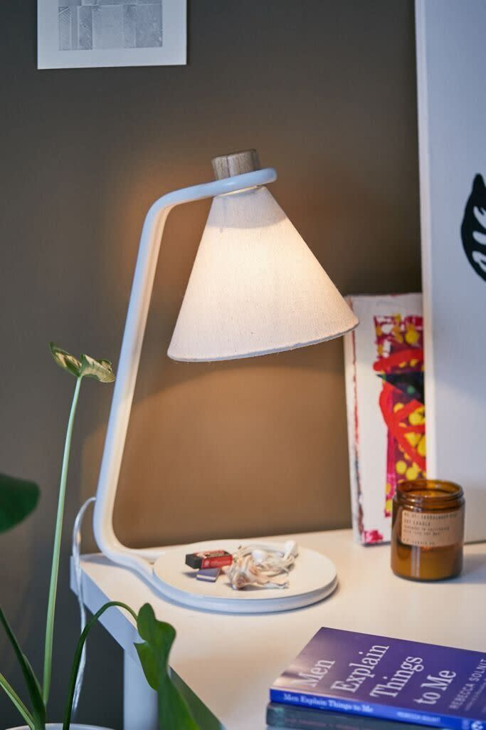 """With a catch-all dish base, you can finally organize all the paper clips, bobby pins and thumb tacks you keep on your desk with this lamp. It's retro-inspired, so it'll go with your <a href=""""https://www.huffpost.com/entry/best-sites-for-midcentury-modern-furniture_n_596fcbdce4b062ea5f8ef4f3"""" data-ylk=""""slk:mid-century modern aesthetic"""" class=""""link rapid-noclick-resp"""">mid-century modern aesthetic</a>. You can plug in this lamp, which requires a <a href=""""https://fave.co/3iyjiJL"""" rel=""""nofollow noopener"""" target=""""_blank"""" data-ylk=""""slk:60-watt bulb"""" class=""""link rapid-noclick-resp"""">60-watt bulb</a>. But the shade is already included. <a href=""""https://fave.co/33BXG9s"""" rel=""""nofollow noopener"""" target=""""_blank"""" data-ylk=""""slk:Find it for $59 at Urban Outfitters"""" class=""""link rapid-noclick-resp"""">Find it for $59 at Urban Outfitters</a>."""